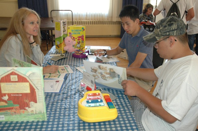 Nancy Hill, Aberdeen Proving Ground Federal Credit Union representative, talks to Ben Xu, 15 and David Yip, 16, about child care expenses during Mad City Money, an activity designed to teach teens about budgeting.