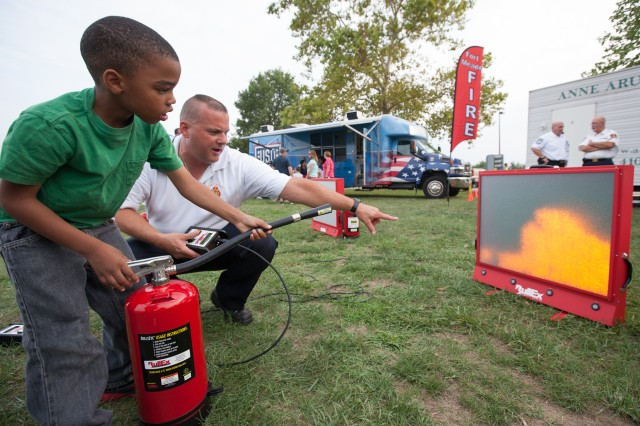 Tyler Rucker-Pickett, 6, puts out a virtual fire with the help of Fort Meade Fire Capt. John Trottman.  The simulator used a laser direction-sensing fire extinguisher to teach children how to properly extinguish a fire.