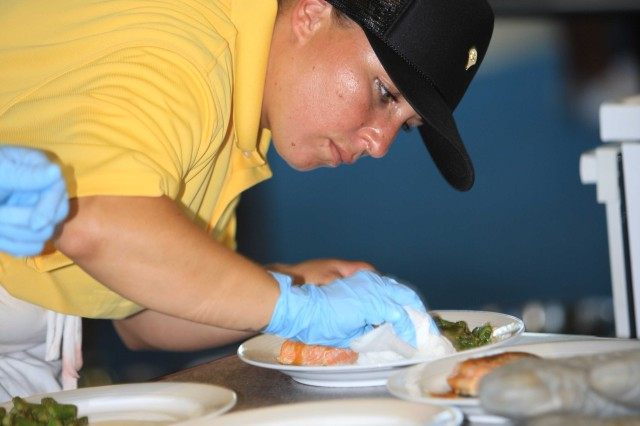 Spc. Metzaly Ayalavargas, assigned to 1-1 ADA, carefully reviews each entree for presentation during the inaugural island-wide, interservice cook-off held July 28 at Camp Foster, Okinawa.