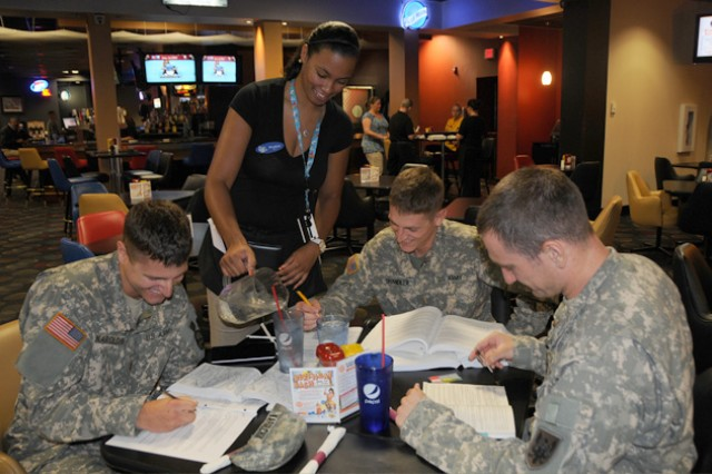 Phylicia Thomas, a waitress at The Landing Zone, serves her guests, 2nd Lt. Michael Karolchik, 2nd Lt. Thomas Chandler and W01 Christopher Scott B. Co., 1st Bn., 145th Avn. Rgt., at lunchtime.
