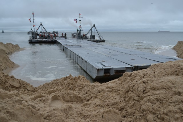 """A floating causeway pier, pushed by Warping Tugs, moves toward the beach at Fort Story, Va., Sept. 24, 2011. The causeway will """"stab the beach"""" creating a pier. The 7th Sustainment Brigade's Joint Logistics Over-the-Shore exercise, Fall Trident, spearheaded by the 11th and 24th Transportation Battalions, at Joint Base Expeditionary Little Creek-Fort Story, Va."""