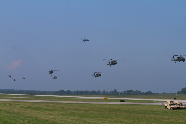 FORT CAMPBELL, Ky- A lone U.S. Army AH-64 Apache flies overhead as U.S. Army UH-60 Blackhawk helicopters from the 159th Combat Aviation Brigade, 101st Airborne Division, loaded with the Soldiers from 2nd Battalion, 506th Infantry Regiment, 4th Brigade Combat Team, 101st Abn. Div., conduct an air assault, August 7, 2012 in preparation for the Week of Eagles, at Fort Campbell, Ky. (U.S. Army photo by Maj. Kamil Sztalkoper, 4th Brigade Combat Team Public Affairs)