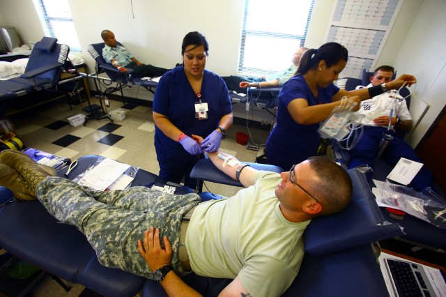 Staff Sgt. Nicholas Krohn (foreground) donates blood while phlebotomist Daisy Mayer monitors the procedure Aug. 3 at B Battery, 2nd Battalion, 6th Air Defense Artillery's blood drive in Building 2750 Miner Road. Also donating were (in background, from left) Spc. Jordan Malubay, Spc. Jedidiah Rash and Spc. Shawn Kratz, who was assisted by phlebotomist Thea Alexander.