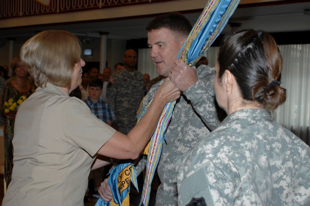 Army Lt. Col. Patrick E. Taylor receives the organization's colors from DLA Troop Support Acting Commander Navy Rear Adm. Patricia Wolfe during his Assumption of Command ceremony July 8 in Kaiserslautern, Germany.