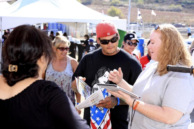 Heather Rogers (right) of Bristol Environmental Remediation Services conducts a short survey with race fans. The tablet based program helps capture what types of off-road activities they participate in on public lands and where they might have seen ordnance. The area is part of the former California-Arizona Maneuver Area, where Gen. George S. Patton, Jr., trained a million troops for desert warfare.