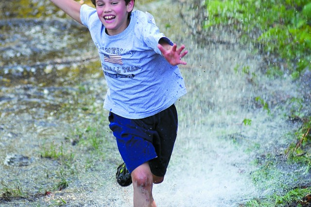 Declan Dobos, 9, enjoys the cool spray while making his way through the first mud obstacle.