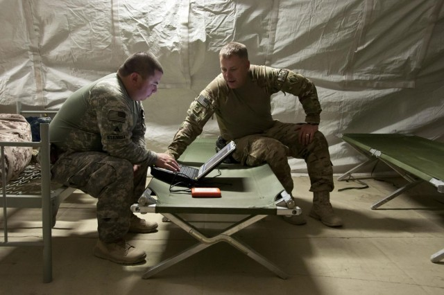 David Nishimura (left) and Sgt. 1st Class Gary Malkin, from the 565th Engineer Detachment (FEST-A) check their equipment in a tent on Combat Outpost Little Blue before conducting a route reconnaissance mission in Shah Wali Kot district, Kandahar province, Afghanistan on July 26.