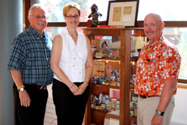 Dr. Michael F. Cadin, left and his brother, John W. Cadin, gather with Michelle R. Zegarelli, Fort Drum DENTAC supervisory administrative officer, after donating historical dentistry items to Stone Clinic.