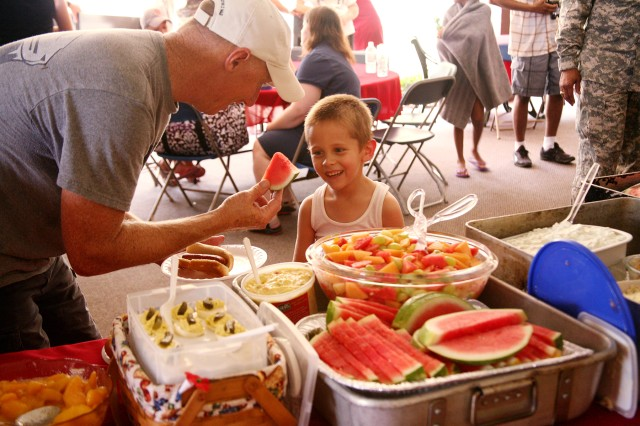 Ricky Judy, U.S. Army Space and Missile Defense Command/Army Forces Strategic Command, offers KayCee Chaney a slice of watermelon during the Survivor Outreach Services summer bash at the Family Morale, Welfare and Recreation building Aug. 4.