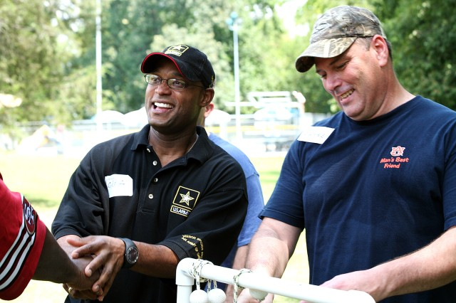 Lt. Col. Greg Ash, deputy chief of staff G-1, left, and rope toss opponent Chief Warrant Officer 2 James Joyner, Network Enterprise Management Division, congratulate each other and their teammates following a good natured competitive game during the Survivor Outreach Services summer bash at the Family Morale, Welfare and Recreation building Aug. 4. Ash and Joyner both work at the U.S. Army Space and Missile Defense Command/Army Forces Strategic Command.