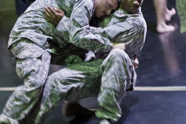 "Spc. Regis Kessler, a resident of Pittsburgh, practices a take down on fellow 316th Sustainment Command (Experitionary) member, Sgt. Andre Patterson, a resident of Swissvale, Pa., during Modern Army Combatives Program Level One training at Camp Arifjan, Kuwait, Aug. 6 through 10. ""My favorite part so far has getting to throw around Patterson, cause he's a lot bigger than me."""