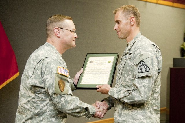 Colonel R. Eric Fletcher, Project Manager Force Protection, left, hands the charter for Product Manager Force Sustainment Systems to Lt. Col. Ross Poppenberger during an Aug. 9 ceremony at Natick Soldier Systems Center.