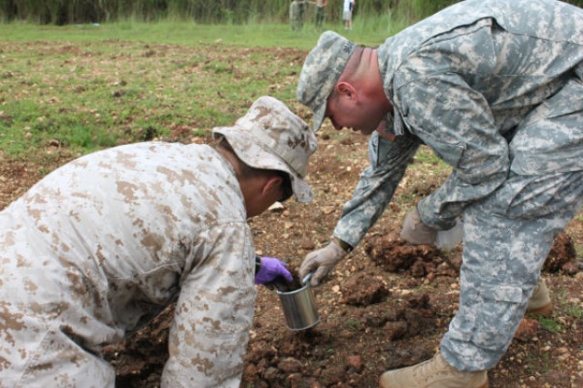 Marine Staff Sgt. Kevin Hunsinger, right, and Army Staff Sgt. Casey Brantner take soil samples of an explosion site during the FBI Post Blast Conference August 7-9, 2012, at U.S. Naval Base Guam.