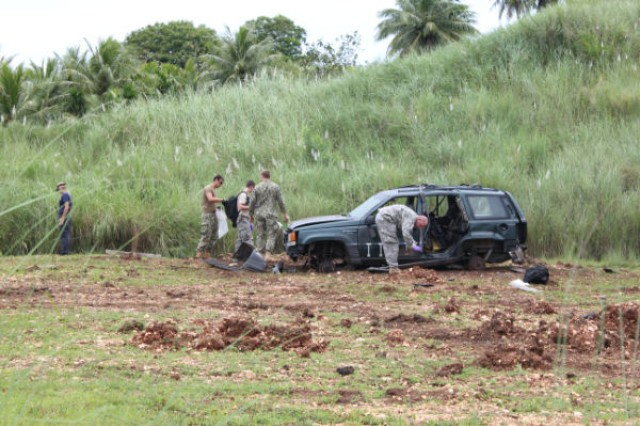 Joint service members participate as evidence collection teams during a training event at the FBI Post Blast Conference held August 7-9, 2012, at U.S. Naval Base Guam. Students collected relavent evidence from an explosion to the vehicle.