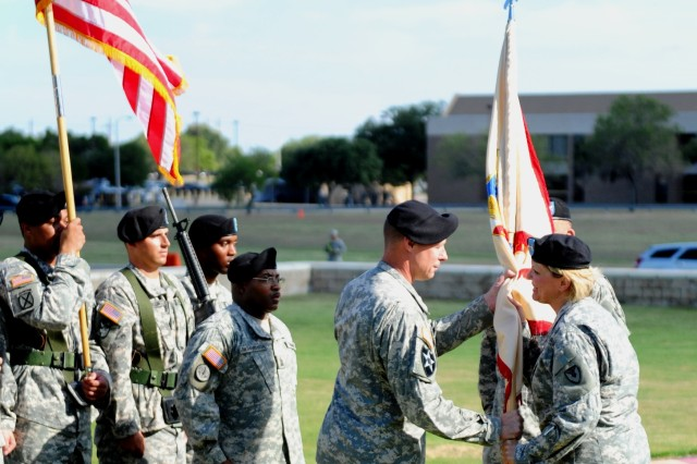 "Maj. Gen. Patricia E. McQuistion, Army Sustainment commanding general,  passes the colors to Col. Steven  Allen, incoming commander of the ""Mighty""  407th AFSB, during a change of command ceremony on July 26 at Fort Hood, Texas. (Photo by Erin Rogers, III Corps and Fort Hood Public Affairs)"