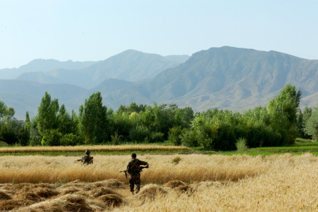 Two soldiers of Weapons Company, 3rd Kandak, 201st Corps, Afghan National Army, move through a field outside the village of Yusof Khyel in Afghanistan's Wardak province, to pull security while the rest of their element searched houses in the village during Operation Assaly II, July 26, 2012. During the operation, elements of the 3rd, 4th and Weapons Companies, 3rd Kandak, 201st Corps, Afghan National Army, led the patrols from start to finish.
