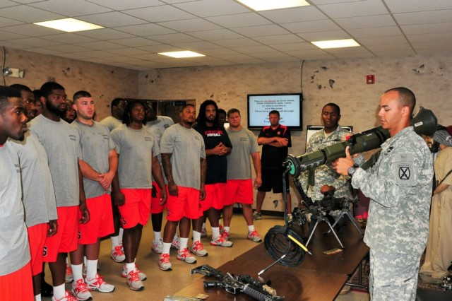 A Soldier from 2nd Battalion, 87th Infantry Regiment, 3rd Brigade Combat Team, 10th Mountain Division, demonstrates the AT-4 anti-tank weapon to players from Syracuse University's football team. The team is at Fort Drum, N.Y. for a weeklong preseason training camp.