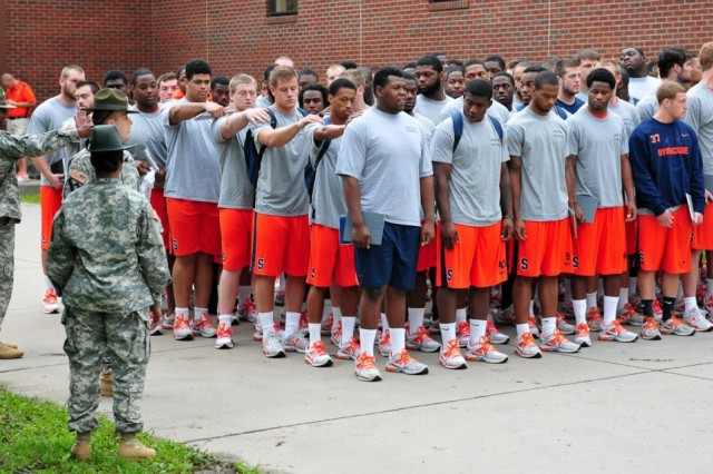 Football players from Syracuse University's football team practice standing in formation at their barracks at Fort Drum, N.Y., with help from former drill sergeants now currently assigned to the 3rd Brigade Combat Team, 10th Mountain Division.  The football team is at Fort Drum for a weeklong preseason training camp, and is working with Soldiers on military training.