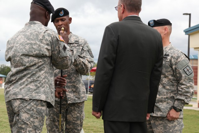 Command Sgt. Maj. Sultan A. Muhammad, Ordnance Corps regimental command sergeant major, passes the noncommissioned officer sword to Command Sgt. Maj. Edward C. Morris, 59th Ordnance Brigade command sergeant major, to signify his relinquishment of responsibility Aug. 10. Muhammad will be reporting to the Defense Logistics Agency, Fort Belvoir, Va., where he will be the senior enlisted advisor.
