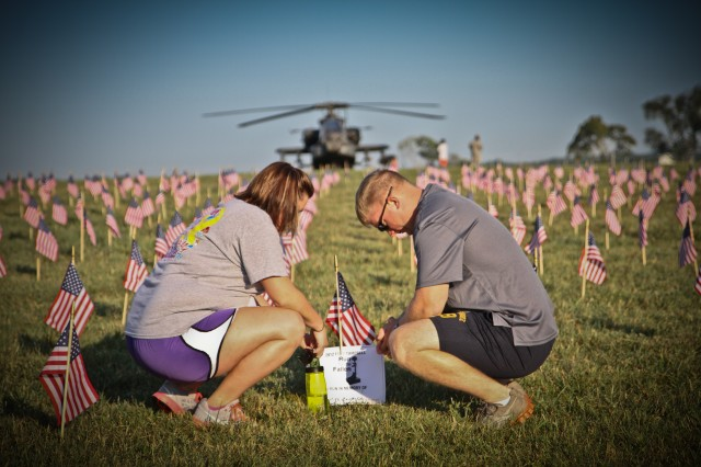 Michelle Leibold, wife of Spc. Jeff Leibold, an infantryman with Headquarters and Headquarters Company, 2nd Brigade Combat Team, 101st Airborne Division (Air Assault), and his wife Michelle Leibold, pay their respects to a fallen comrade during the Run for the Fallen, Aug. 11, 2012, at Fort Campbell, Ky. The run is part of the Week of the Eagles 2012 that honors today's Soldier's, military families, veterans and Gold Star families.
