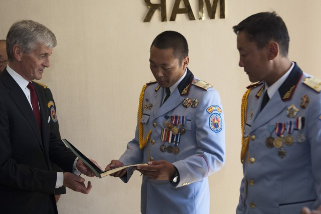 Secretary of the Army John McHugh presents certificates to two Mongolian soldiers during a visit to the Mongolian Ministry of Defense Aug. 13, 2012.  The Soldiers were recognized for valor for actions they took to prevent a vehicle borne explosive device from entering the coalition base they were guarding in Iraq, saving countless lives.  (U.S. Army photo by Spc. John G. Martinez)