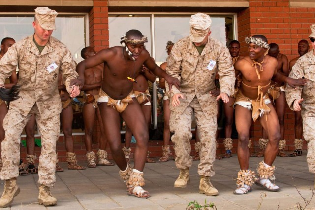 Pfc. Kevin Corey, Lance Cpl. Eric Whisman, both from Anchorage, Alaska, and Lance Cpl Michael S. Chafin from Wasilla, Alaska, three Marines with Company D, Antiterrorism Battalion out of Anchorage, Alaska, join Botswana Defense Force soldiers as they perform a traditional dance during culture day at Southern Accord 2012. U.S. service members are participating in the combined, joint exercise with the BDF in order to enhance interoperability and strengthen their partnership. (U.S. Army photo by Sgt. Adam Fischman, 139th MPAD)