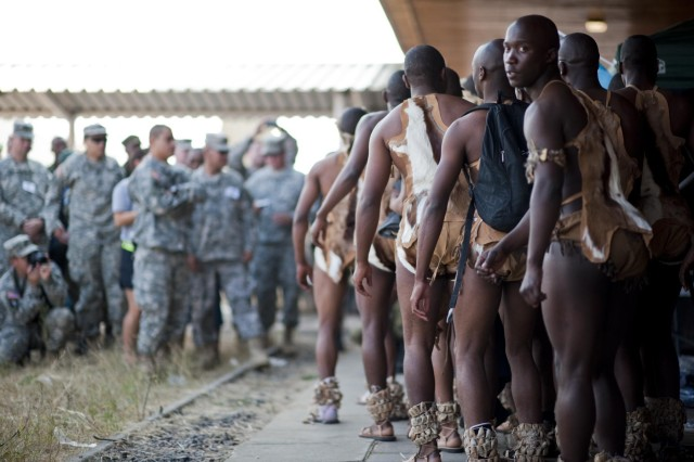 U.S. service members prepare to watch a dance performance by soldiers of the Botswana Defense Force dressed in ceremonial garb at Thebephatshwa Air Base in the Republic of Botswana, Aug. 5, 2012. Cultural day allowed soldiers, Marines, airmen, and sailors operating in Southern Accord 2012 to interact with members of the Botswana Defense Force and local civilians in the community. (U.S. Army photo by Sgt. Adam Fischman)