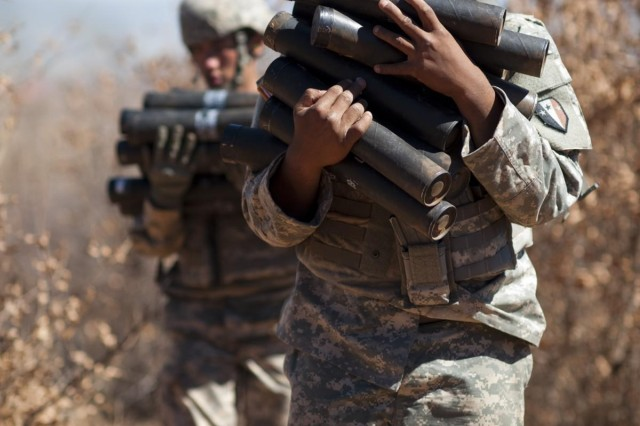 Pfc. Brandon Wood with Company C, 1st Battalion, 114th Infantry Regiment, out of New Jersey, carries 60mm mortar tubes back from his firing location during a field training exercise at Southern Accord 2012, Aug. 10, 2012, at Shoshong Range in Botswana. SA12 is a combined, joint exercise designed to enhance military capabilities and interoperability between U.S. military forces and the Botswana Defense Force.