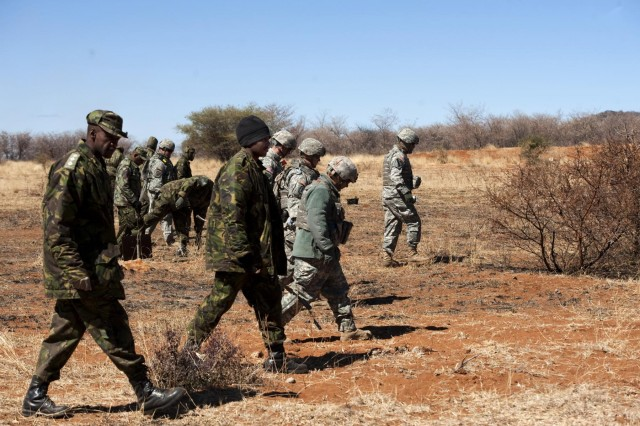 Botswana Defense Force soldiers and U.S. soldiers work together to clear unexploded ordnance from the Shoshong Range in Botswana, Aug. 7, during Southern Accord 2012. SA12 is a U.S. Africa Command-sponsored, U.S. Army Africa-led combined, joint exercise designed to enhance military capabilities and interoperability between U.S. military forces and the BDF. It has played a key role in military-to-military activities to demonstrate the strong partnership between host country militaries. (U.S. Army photo by Sgt. Adam Fischman, 139th MPAD)