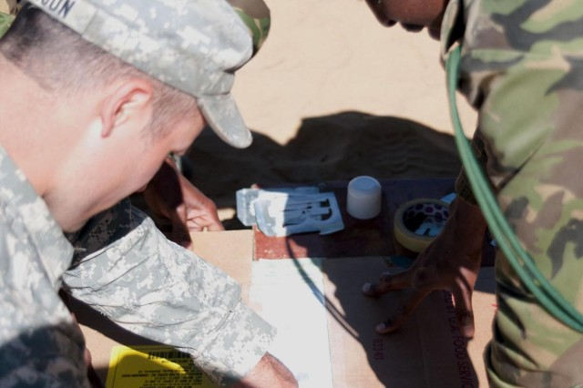 """Sgt. 1st. Class Scott R. Johnson from Chicago, Ill., with the 405th Brigade Support Battalion, Illinois Army National Guard out of Crestwood, Ill., along with members of the Botswana Defense Force, construct a """"ground guide"""" and speed limit sign as an added safety precaution for the motor pool at Southern Accord 2012. (Photo by Army Sgt. Charlie Helmholt, 139th MPAD)"""