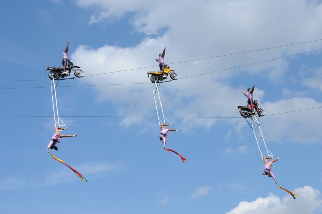 With no hands, male members of the Weisheit family tightrope troupe ride their motorcycles backward along a wire suspended 40 meters in the air, while their sisters hang gracefully below at the 55th Annual German-American Volksfest in Grafenwoehr, Germany, Aug. 3-5.