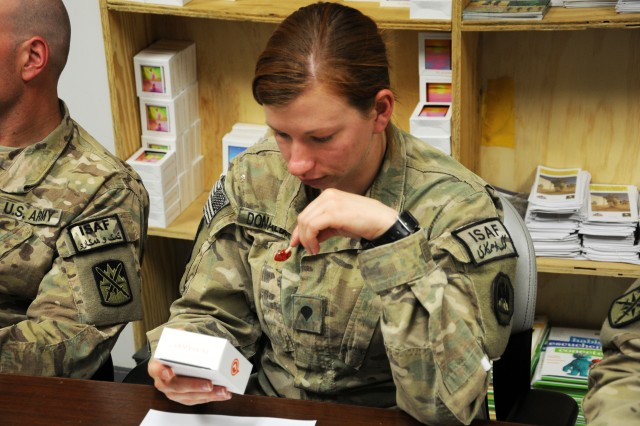 Spc. Larre A. Donaldson, a combat medic with the 1086th Transportation Company, reads the instructions on the back of a playaway listening device, Aug. 7, 2012, at Bagram Airfield, Afghanistan. Combat medics give the listening device to their patients for relaxation treatment in order to combat stress and anxiety.