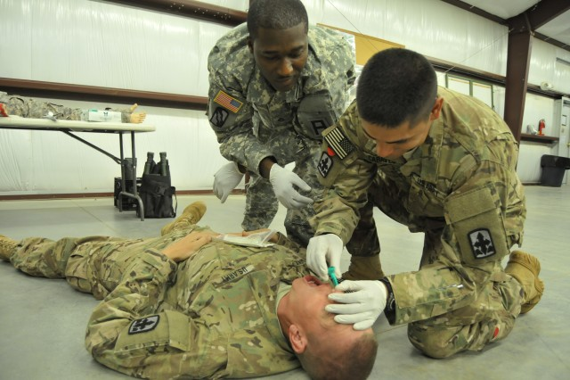 Staff Sgt. Tremmelle Gibson, a medic with the 2-351st Regiment Battalion 158th Infantry Brigade, looks on while Sgt. Edgar A. Caraveo, a field artilleryman with the 29th Brigade Combat Team, opens Cpl. Ian M. Hetzel's airway. The training is part of a Combat Life Saver course the Soldiers underwent in preparation to deploy on a Security Force Advise and Assistance Team to Afghanistan. (Photo by US Army Sgt. Vannessa L. Josey)