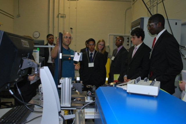 The combustion research facility in the Vehicle Technology Directorate is used to investigate spray and combustion characteristics of JP-8 and alternative fuels. The research facility contains a high temperature pressure vessel, which is used to produce temperatures and pressures typically found in compression ignition engines.  Dr. Matthew Kurman, an ORAU Postdoctoral Research Fellow within the VTD, explains to students how to detect radical species in flames using laser diagnostics.