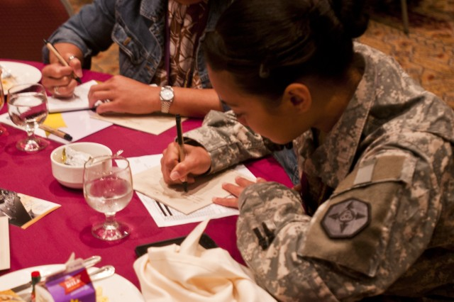 Capt. Cathleen Topasna, of the 143 Expeditionary Sustainment Command, writes down some future goals during the keynote address at a Yellow Ribbon Reintegration event in Orlando, Fla., August 11.