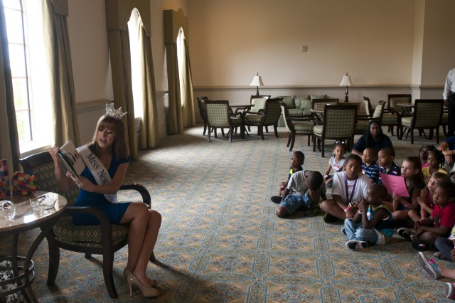 "Miss North Carolina, Arlie Honeycutt, met with military children at a Yellow Ribbon Reintegration event in Orlando, Fla., August 11. She read a couple stories to the youngest group, pictured here, and with the older group, she answered questions about the Miss America program and what it is to be Miss North Carolina. ""It was so exciting to get to know so many of our service members, to get to interact with their kids and their families,"" she said."