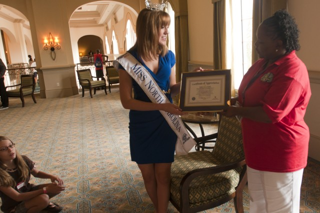 Miss North Carolina, Arlie Honeycutt, is presented with a Certificate of Appreciation from Jennifer Stevens of the 81st Regional Support Command Family Programs at a Yellow Ribbon Reintegration event in Orlando, Fla., August 11. Miss North Carolina spent time reading and interacting with the children of the Soldiers and spouses who were attending the YRRP sessions.