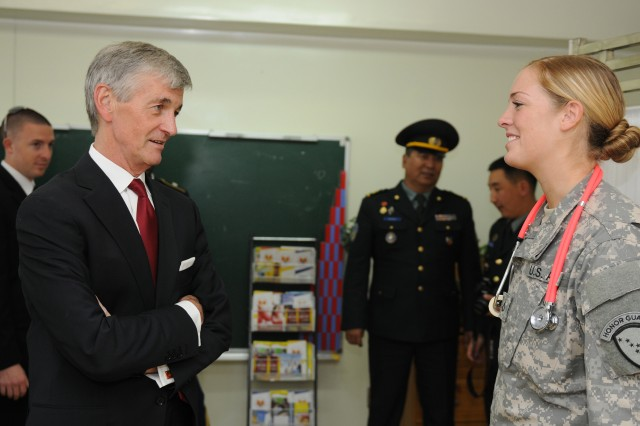 Secretary of the Army John M. McHugh talks with Pfc. Chantal Miller, a medic in the Alaska Army National Guard Medical Detachment, at the medical clinic during his visit of the various Khaan Quest 12 exercise locations in and around Ulaanbaatar, Mongolia, Aug. 14, 2012. Khaan Quest is a regularly scheduled, multinational exercise sponsored by the U.S. Army Pacific and hosted annually by the Mongolian Armed Forces. Photo: Sgt. Edward Eagerton, 134th Public Affairs Detachment, Alaska Army National Guard.