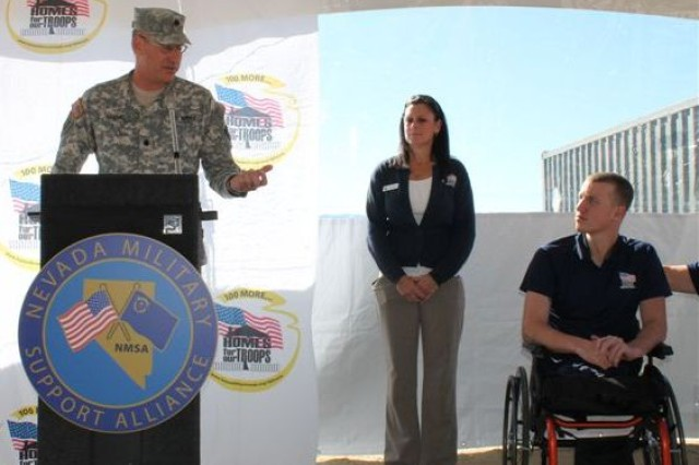 Lt. Col. Craig M. Short, commander of Hawthorne Army Depot, speaks at house-raising as wounded warrior Tim Hall listens.