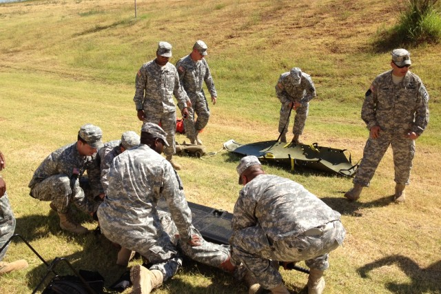 Sgt 1st Class William Dame, right, and Sgt 1st Class Rodarial Foster, standing left, both members of Medical Training Task Force, 479th Field Artillery Brigade, Division West, observe Soldiers of 3rd Training Support Battalion, 290th Regiment, 479th Field Artillery Brigade, Division West, transfer a simulated casualty from a rescue sled stretcher to a litter during Combat Lifesaver training last month in Oklahoma City. The 3-290th Soldiers train mobilizing Army National Guard and Army Reserve units on convoy live fire and mounted gunnery training at Fort Hood, Texas, and must be CLS certified because of the risks associated with live-fire training. (Photo by Capt. Bradley Mattison, 479th Field Artillery Brigade, Division West)