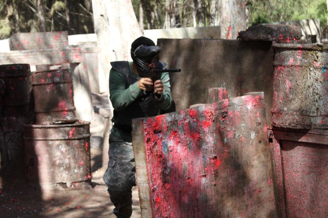 "WAIMANALO, Hawaii "" Spc. Nikolas Revette, lab technician, U.S. Army Health Clinic-Schofield Barracks, defends his position during a paintball competition, Aug. 8, at Bellows Air Force Station, here. The competition was part of Tripler Army Medical Center's Department of Ministry and Pastoral Care's spiritual fitness event, Paintball and Proverbs."