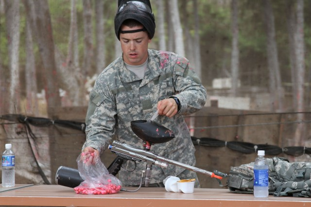 "WAIMANALO, Hawaii "" Cadet Bradley Wilson, Reserve Officers' Training Corps, who is spending a 3-week internship with Medical Company A, Troop Command, Tripler Army Medical Center, loads his paintball gun during a competition, Aug. 8, at Bellows Air Force Station, here. The competition was part of TAMC's Department of Ministry and Pastoral Care's spiritual fitness event, Paintball and Proverbs."