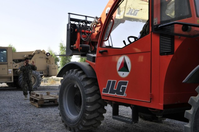 Soldier Sartor, a mechanic with the Kandahar Air Wing, ground guides a fellow mechanic to lift some pallets using a 6K forklift during forklift training taught by soldiers from Headquarters Support Company, 209th Aviation Support Battalion, 25th Combat Aviation Brigade on Kandahar Airfield, Afghanistan, Aug. 11.