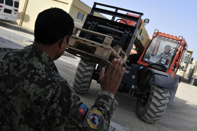 Soldier Sartor, a mechanic with the Kandahar Air Wing, ground guides Afghan Staff Sgt. Yousif to move some pallets using a 6K forklift during forklift training taught by soldiers from Headquarters Support Company, 209th Aviation Support Battalion, 25th Combat Aviation Brigade on Kandahar Airfield, Afghanistan, Aug. 11.
