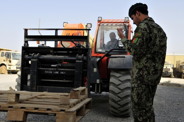 Soldier Azizullah, a mechanic with the Kandahar Air Wing, ground guides Afghan 1st Sgt. Manwar into position to lower some pallets using a 6K forklift during forklift training taught by soldiers from Headquarters Support Company, 209th Aviation Support Battalion, 25th Combat Aviation Brigade on Kandahar Airfield, Afghanistan, Aug. 11.