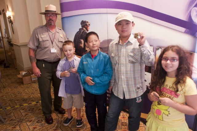Having just been sworn in as Junior Park Rangers, military children show their new park patches and badges from Park Ranger Carl Bertoch during a Yellow Ribbon event in Orlando, Fla., August 12.