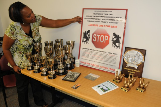 Jane Clements, Army Substance Abuse Program, sets up a display Aug. 10, 2012, of the trophies and plaques that winners will receive at the Swing Fore Life Golf Tournament and the Strike Out Suicide Bowling Tournament in September.