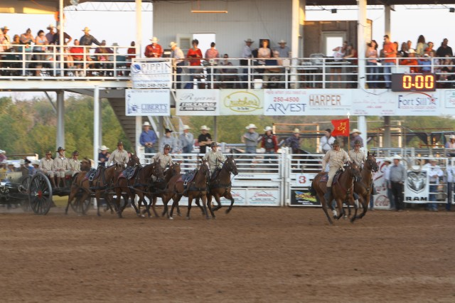 The Fort Sill Field Artillery Half-Section enters the rodeo arena at the start of its performance Aug. 11. The performance during the Saturday military appreciation night was more significant as it demonstrated to Soldiers in attendance what past field artillerymen did during World War I.
