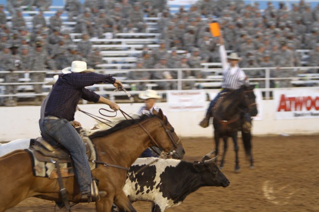 A rodeo competitor attempts to wrestle a steer during one of the events. Once the steer is released from the gates the goal is to wrestle it to the ground as fast as possible.