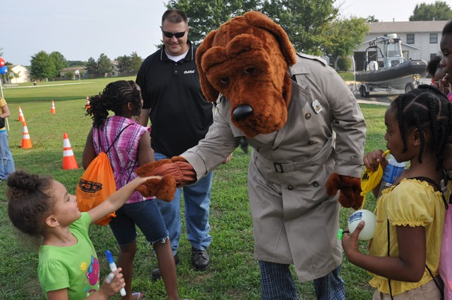 "Mike ""Big Mike"" Farlow and McGruff the Crime Fighting Dog greet neighborhood kids near the McGruff House during Installation National Night Out festivities."